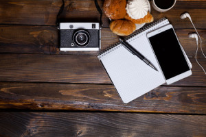 72434398 - camera with headphones with croissants and coffee next to notebook on wooden background
